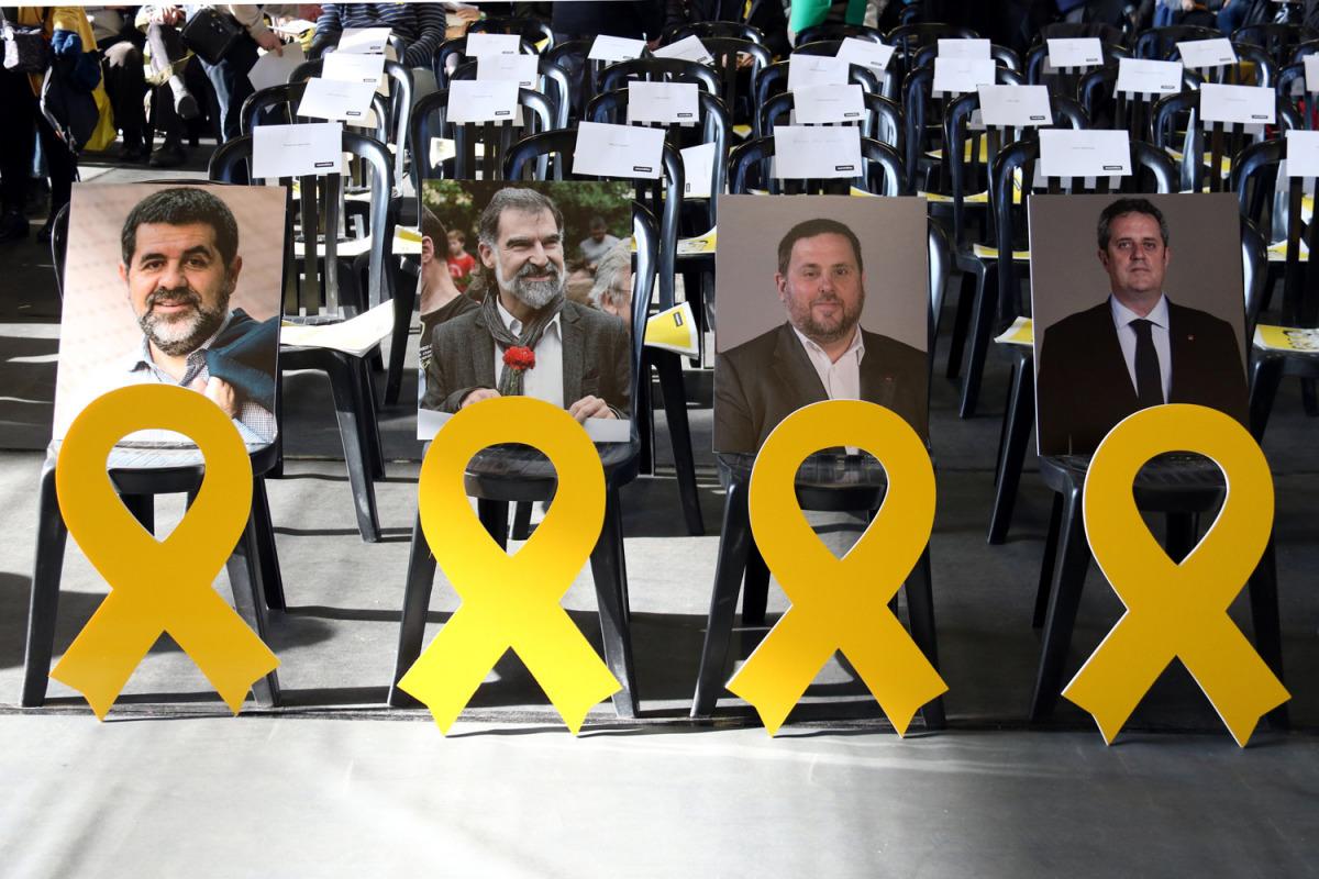 Una fotografia i un llaç groc dels empresonats Jordi Sánchez, Jordi Cuixart, Oriol Junqueras i Joaquim Forn a la primera fila de l'Assemblea General Ordinària de l'ANC