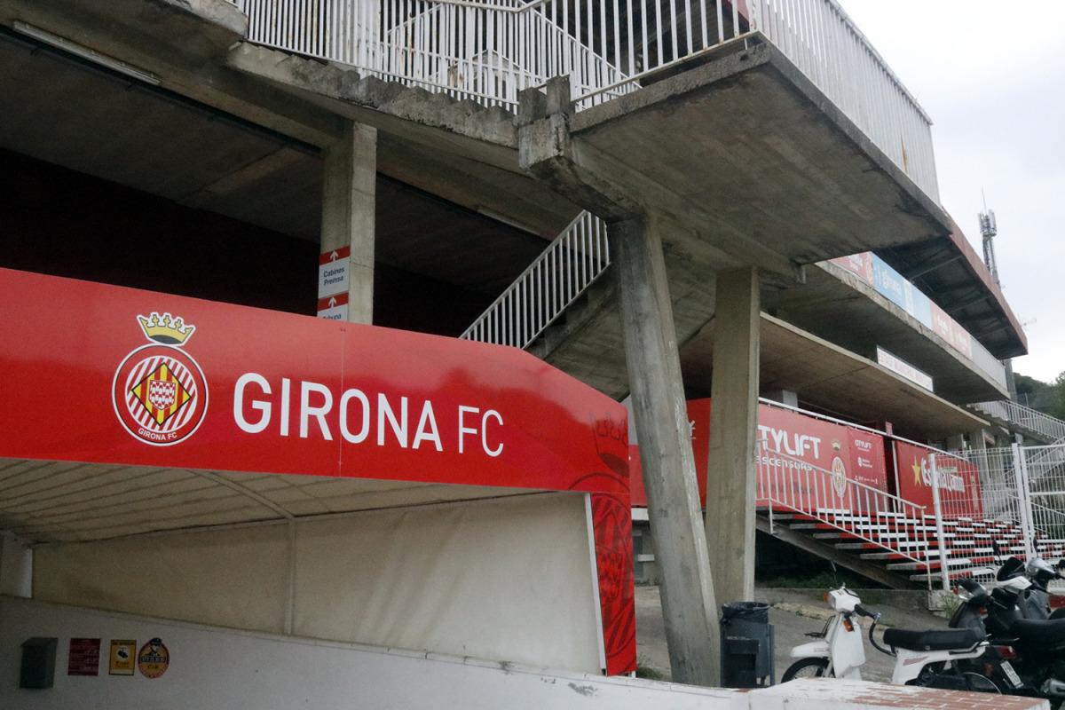 En primer terme, el cartell amb el rètol del Girona FC; al fons, l'estadi de Montilivi