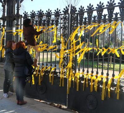 Imatge d'assistents lligant llaços grocs al perímetre del parc de la Ciutadella