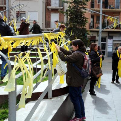 Una noia penja llaços grocs a una tanca de la plaça Ricard Vinyes de Lleida