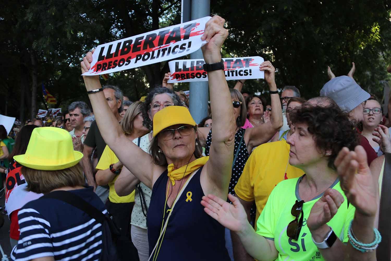 Una dona mostra una pancarta que reclama la llibertat dels presos polítics en una manifestació/ Guillem Roset