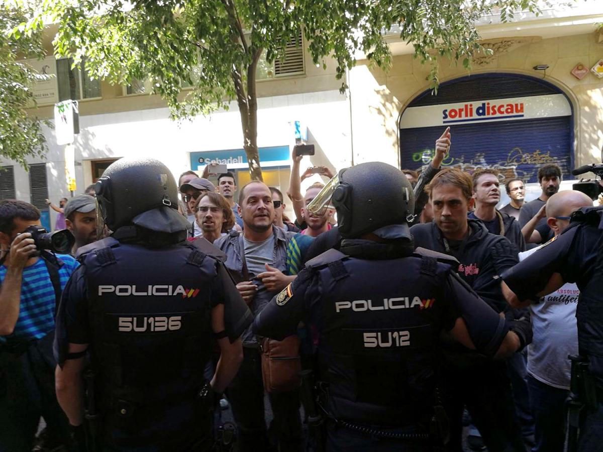 La policia espanyola envoltant la seu de la CUP, mentre simpatitzants criden en contra de l'actuació i en favor de l'1-O, el 20 de setembre de 2017/ CUP