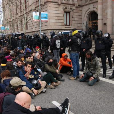 Desenes de membres dels CDR seuen davant d'un grup de Mossos d'Esquadra a la porta principal del TSJC. Imatge del 23 de febrer de 2018