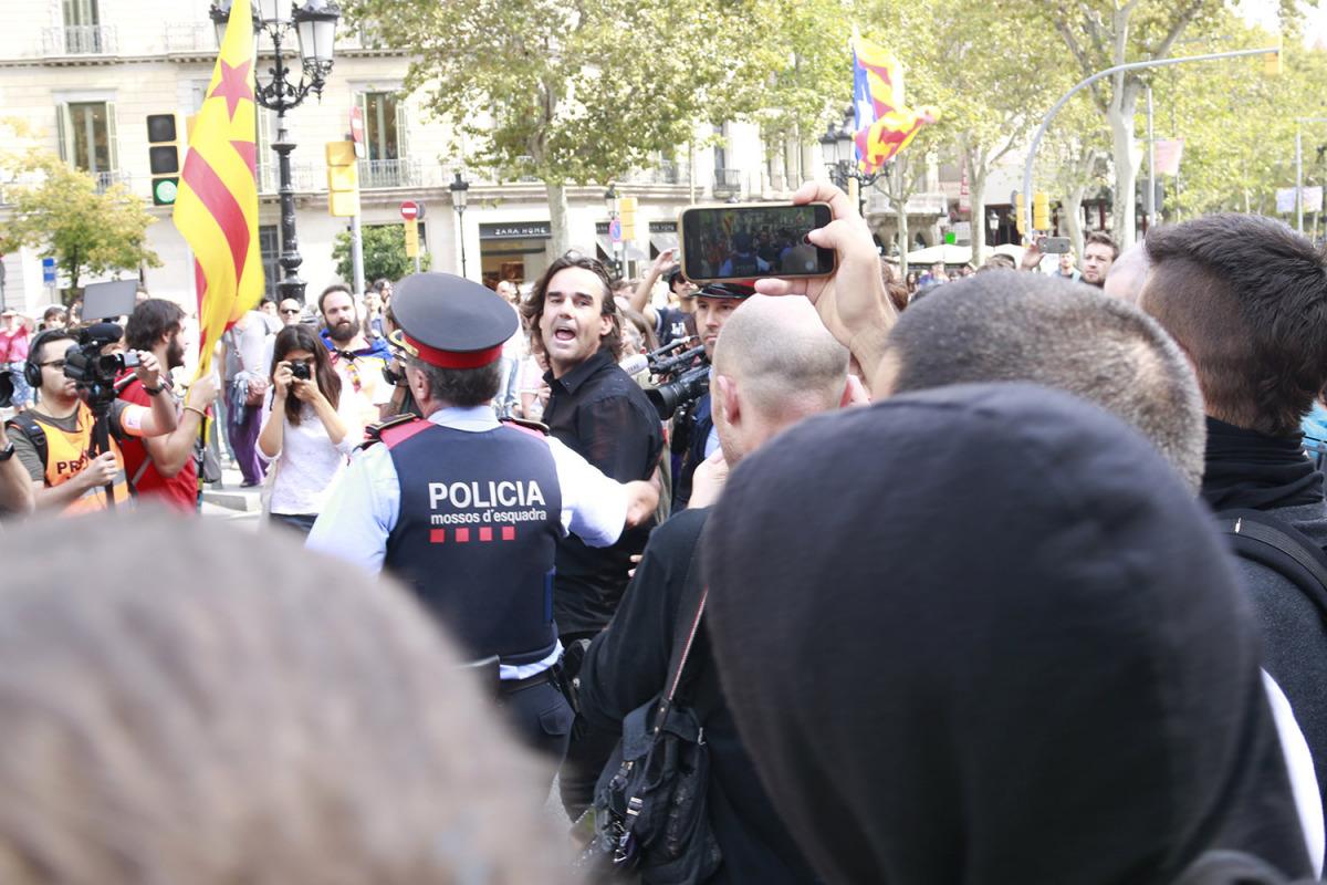 El periodista de 13TV esbroncat per un grup de CDR s'encara als manifestants escortat pels Mossos d'Esquadra/ Laura Fíguls