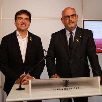 El president d'ERC al Parlament, Sergi Sabrià, i el portaveu de JxCat, Eduard Pujol, somrient en la roda de premsa conjunta/ Guillem Roset