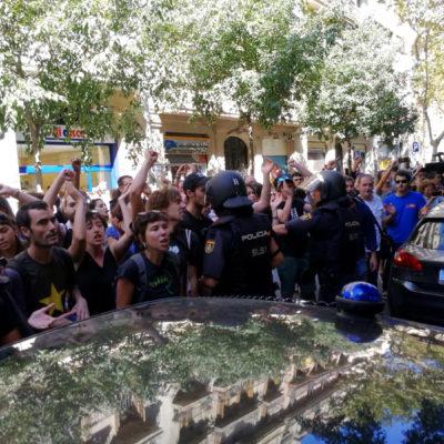 La policia espanyola envoltant la seu de la CUP, mentre simpatitzants criden en contra de l'actuació i en favor de l'1-O, el 20 de setembre de 2017