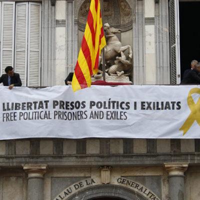 Pla mig del balcó del Palau de la Generalitat en el moment de penjar la pancarta amb el llaç groc el 2 de juny de 2018