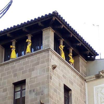 Pla curt on es poden veure quatre llaços grocs lligats al capdamunt de la façana de la Paeria a l'alçada del despatx de la Crida-CUP/ Crida per Lleida