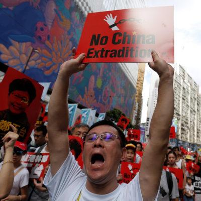 """Pla mig d'un home sostenint un cartell on es pot llegir en anglès """"No China Extradition"""", en una manifestació a Hong Kong"""