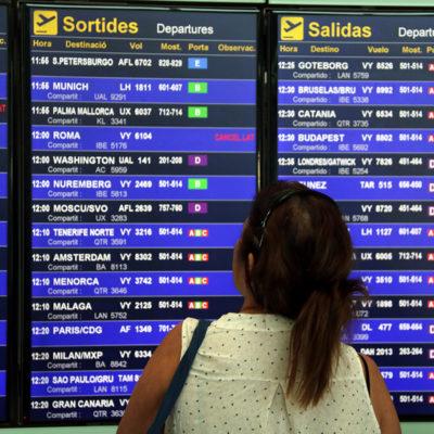 Una usuària de l'aeroport del Prat observant la pantalla de vols