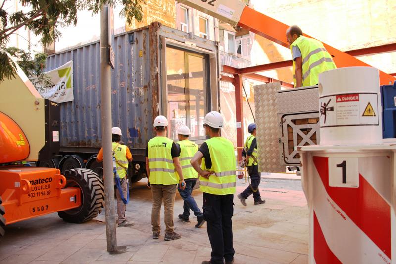 Pla obert d'operaris treballant en la col·locació del primer mòdul habitacional del projecte APROP, al Barri Gòtic