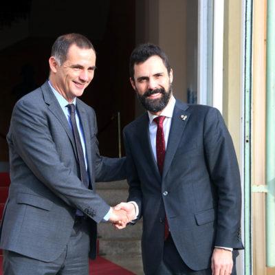 Imatge de Roger Torrent i Gilles Simeoni saludant-se a l'entrada de la seu del Consell Executiu de Còrsega