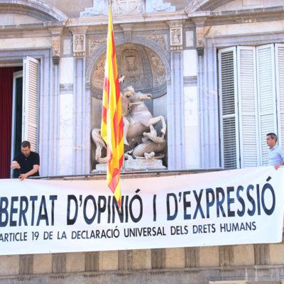 """Membres de l'equip del president del Govern, Quim Torra, pengen la nova pancarta a la façana de Palau: """"Llibertat d'opinió i d'expressió. Article 19 de la Declaració Universal dels Drets Humans"""", a plaça Sant Jaume, el 22 de març de 2019"""