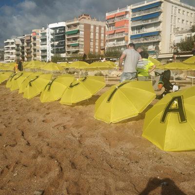 Pla mitjà d'alguns dels para-sols plantats a la platja de Sa Palomera de Blanes aquest diumenge