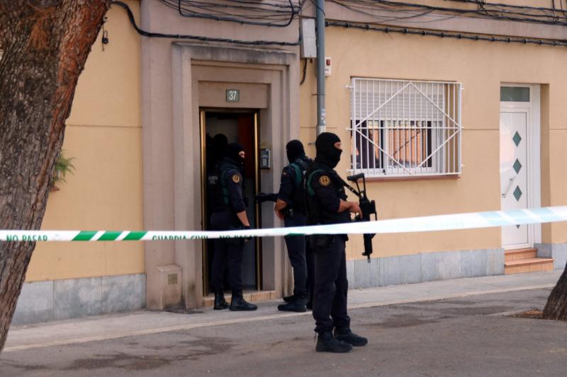 Agents de la Guàrdia Civil a la porta d'un habitatge del carrer Goya de Sabadell on estan duent a terme un escorcoll