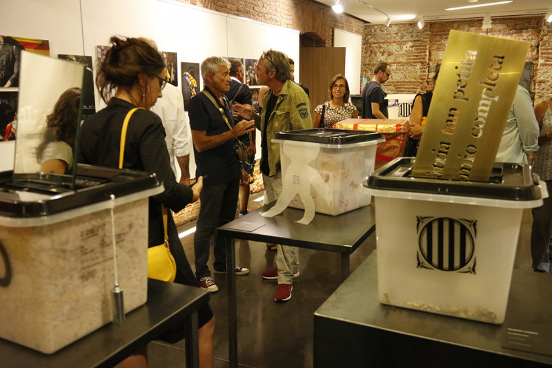 Gent passejant entre l'exposició '55 urnes per la llibertat' a la Casa de la Catalanitat