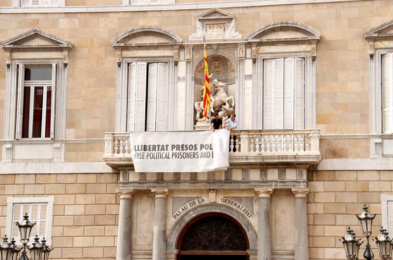 Pla general de la façana de la Generalitat on es veu la pancarta en favor de la llibertat dels presos mig plegada en el moment de treure-la