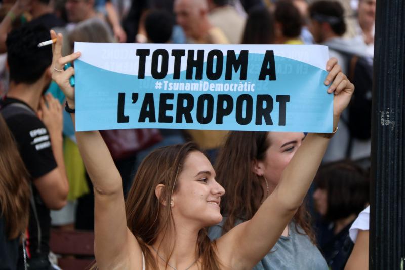 Pla d'una noia que mostra un cartell de Tsunami Democràtic cridant a la gent a mobilitzar-se a l'aeroport