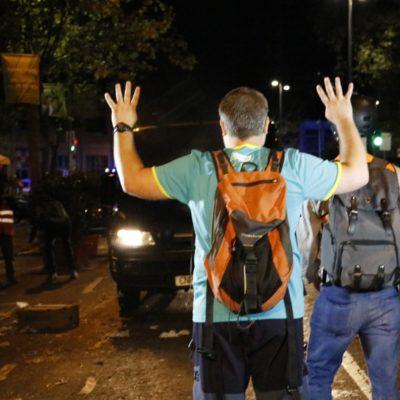 Un manifestant aixeca els braços davant de furgonetes policials el 16 d'octubre del 2019 a Barcelona
