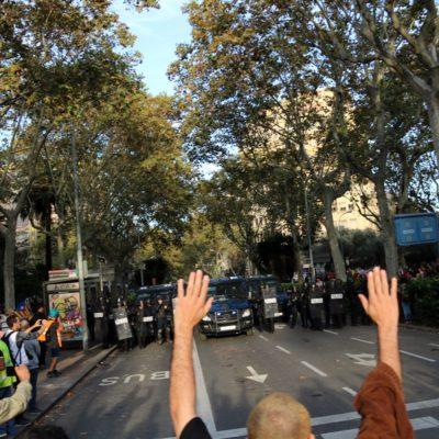 Manifestants amb els braços alçats abans que la policia espanyola inicï les primeres càrregues el 19 d'octubre