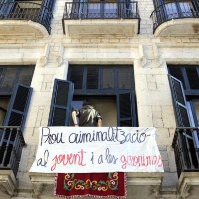 """Pancarta denunciant la """"criminalització"""" del jovent penjada a la façana de l'Ajuntament de Girona"""